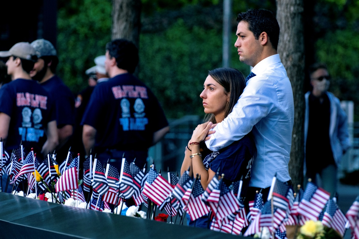 Katie Mascali is comforted by her fiance Andre Jabban as they stand near the name of her father Joseph Mascali, with FDNY Rescue 5, commemorating September 11 attacks, in Manhattan, New York City. [Craig Ruttle via Reuters]