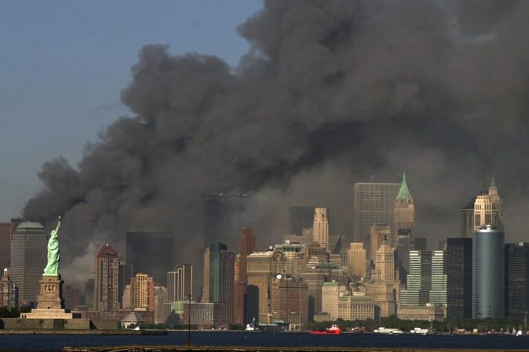Nesta foto de 11 de setembro de 2001, uma densa fumaça sobe no céu por trás da Estátua da Liberdade, embaixo à esquerda, onde ficavam as torres do World Trade Center [Daniel Hulshizer/AP]