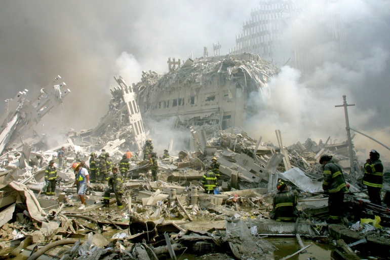 Firefighters make their way through the rubble after two hijacked airliners were crashed into the World Trade Center, bringing down the twin 110-storey towers in New York Tuesday, September 11, 2001 [Shawn Baldwin/AP Photo]