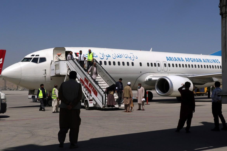 Passengers disembark as they arrive from Kandahar, at Hamid Karzai International Airport in Kabul. [Wali Sabawoon/AP Photo]
