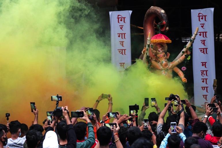 As pessoas levantam seus celulares para registrar os momentos em que um ídolo do deus hindu Ganesha é transportado em Mumbai [Rafiq Maqbool/AP]