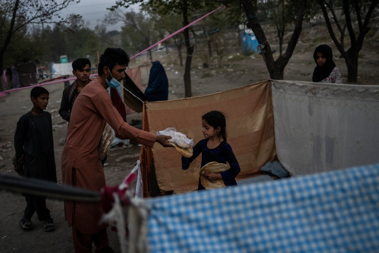 Displaced Afghans distribute food donations at an internally displaced persons camp in Kabul [Bernat Armangue/AP]