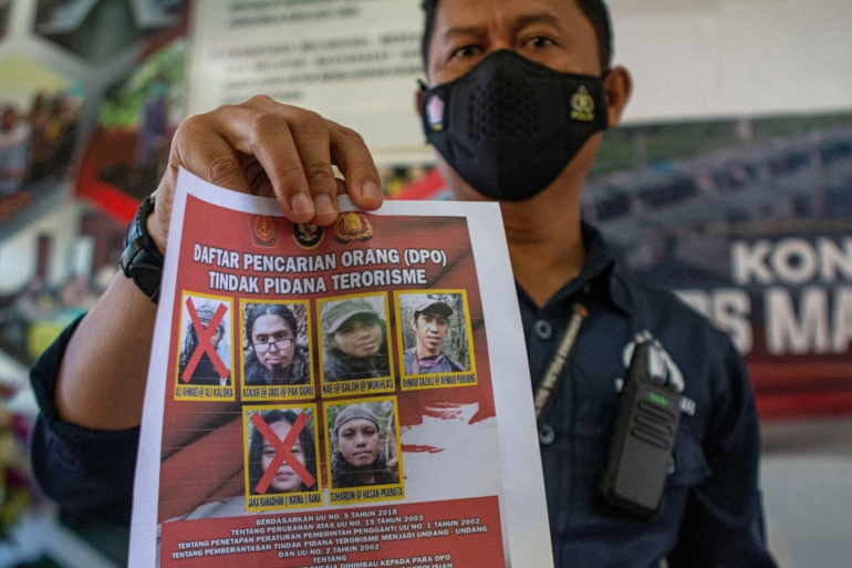 A police officer shows a poster displaying the photos of Ali Kalora, top left, and Jaka Ramadan, bottom left, who were killed during a shoot-out with security forces, in Sulawesi [Mohammad Taufan/AP Photo]