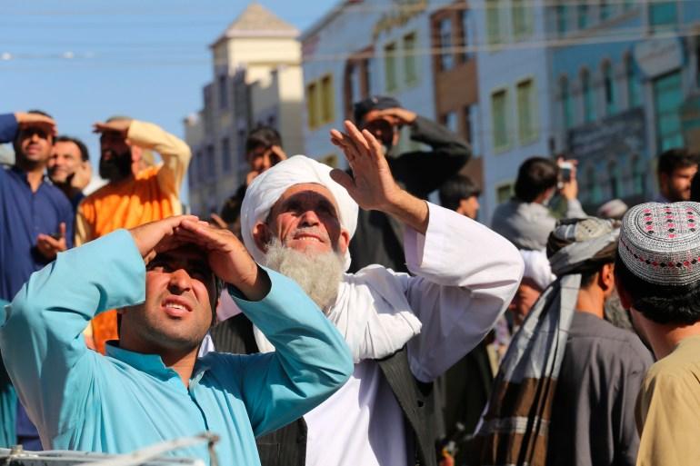 İnsanlar, Herat şehrinin ana meydanındaki bir vinçten Taliban tarafından asılan bir cesede bakıyorlar. [AP Photo]
