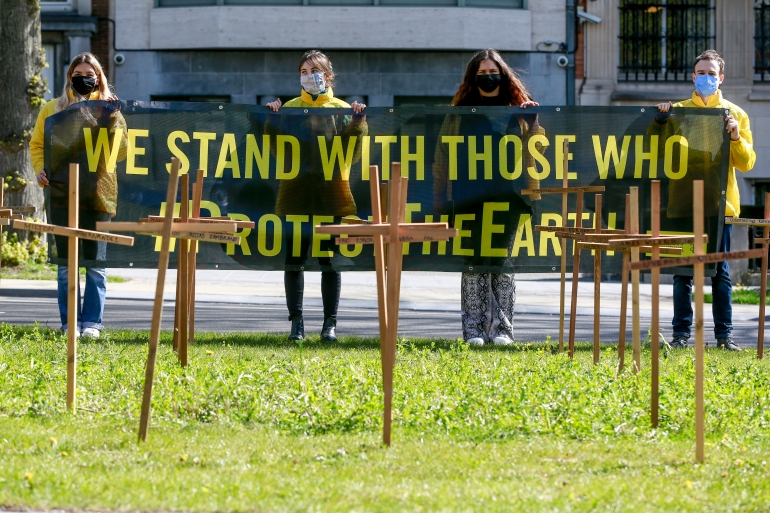 Activists gather around crosses in front of the Colombian Embassy in Brussels, Belgium bearing the names of the 64 environmental defenders murdered in Colombia in 2019 - 2020 was deadlier [File: Stephanie Lecocq/EPA-EFE]