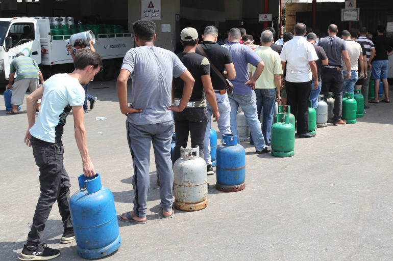 People queue to refill domestic gas cylinders at a petrol station in the Ouzai area of the capital Beirut [Nabil Mounzer/EPA-EFE]