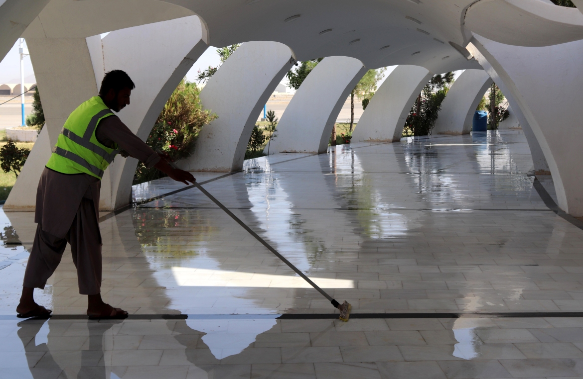 An airport worker sweeps the floor at the terminal after flight operations resumed across Afghanistan, at Ahmad Shah Baba International Airport in Kandahar. [EPA]
