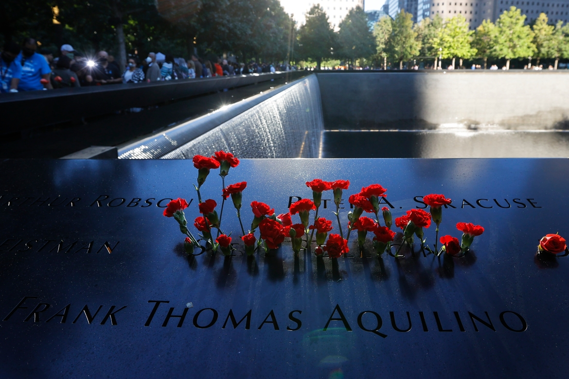 Flowers are seen on the 9/11 Memorial on the 20th anniversary of the September 11 attacks. [Mike Segar via EPA]