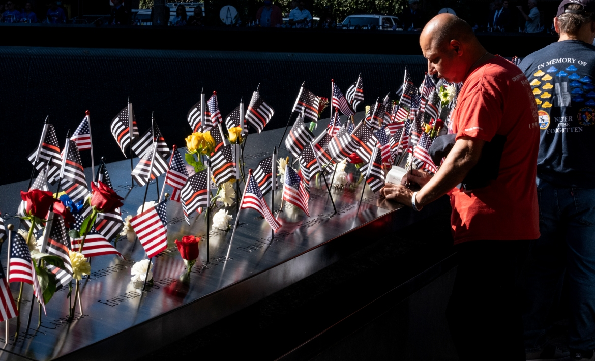 Flags adorn the names of the victims of the attacks of September 11, 2001, during a ceremony at the 9/11 Memorial and Museum's memorial pools in New York. [Craig Ruttle/EPA]