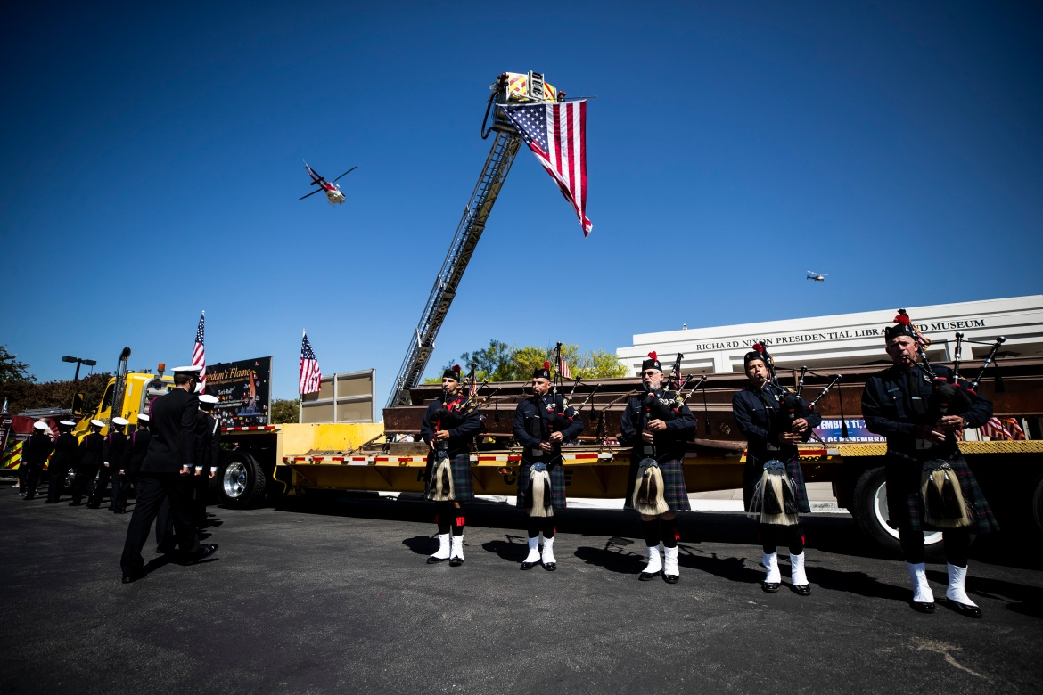 Bagpipers perform in front of a truck carrying 23 tonnes of steel from the structure of the Twin Towers parked in front of The Richard Nixon Library and Museum during the commemoration of the 20th anniversary of the 9/11 attacks in Yorba Linda, California. [Etienne Laurent/EPA]