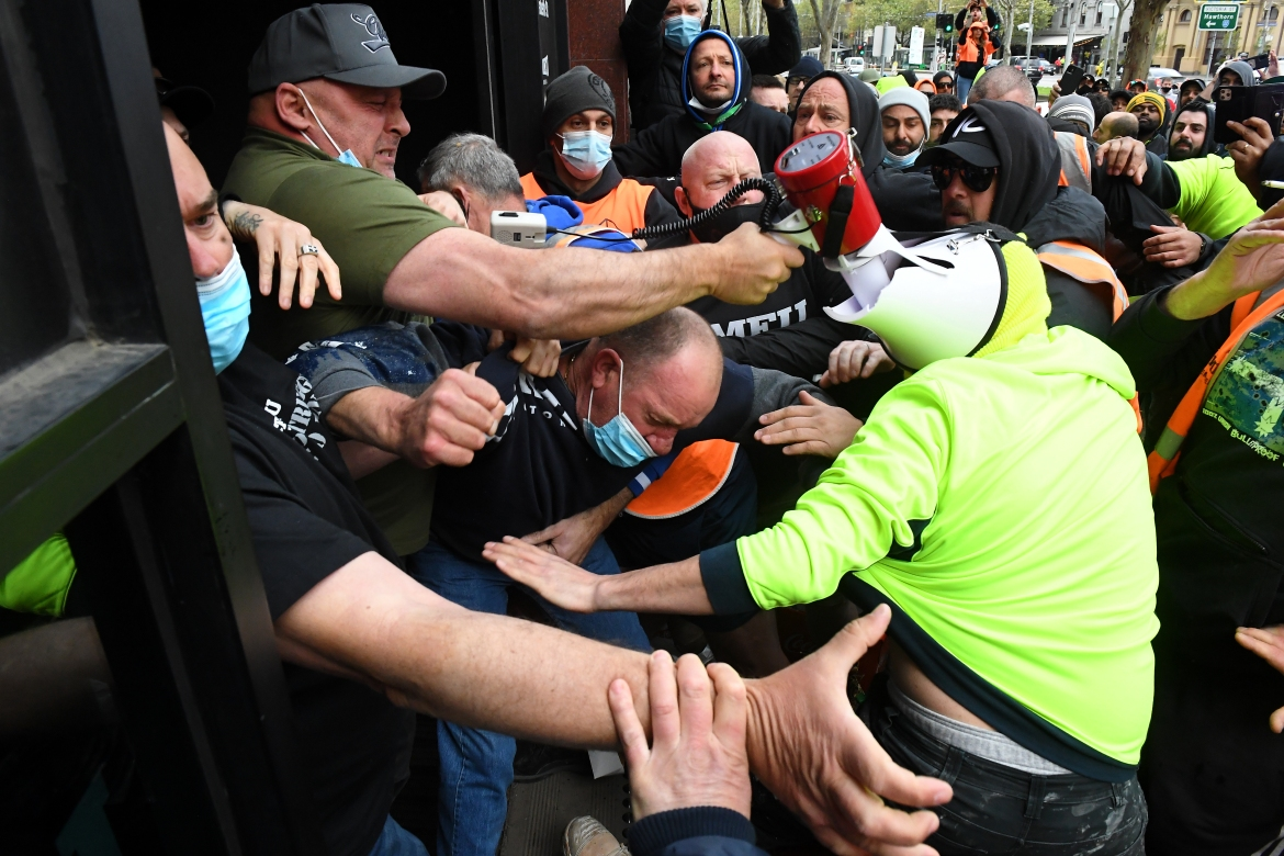 Construction workers clash with union representatives in front of Construction, Forestry, Maritime, Mining and Energy Union (CFMEU) headquarters in Melbourne. [James Ross/EPA]